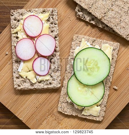 Wholemeal rye crispbread with brie cheese radish and cucumber slices photographed overhead with natural light