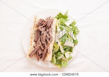 pulled brisket sandwich with a side caesar salad