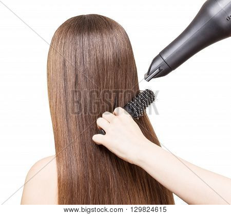 Drying long brown hair with a hairdryer and comb isolated on white background.