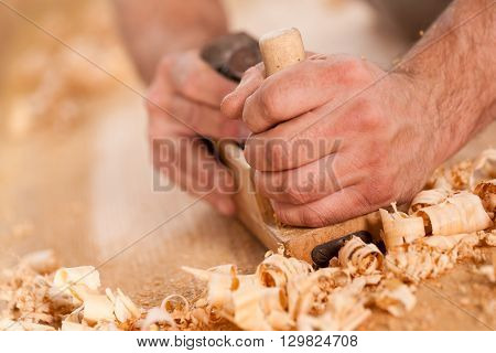 Woodworker Hands Shaving With A Plane