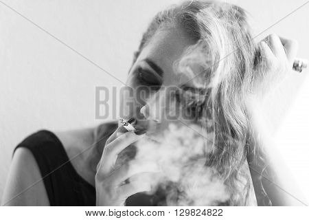 Black and White portrait of pensive young woman smoking