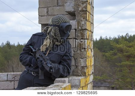 Airsoft player in black mask holding position in ruins