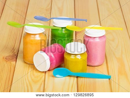 Glass colorful jars of baby food on a background of light wood.