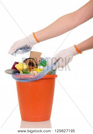Women's hands are removed from the bucket bag with household waste isolated on white background.