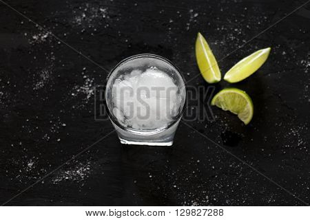Cocktail vodka or gin with ice and lime on a dark background top view with copy space