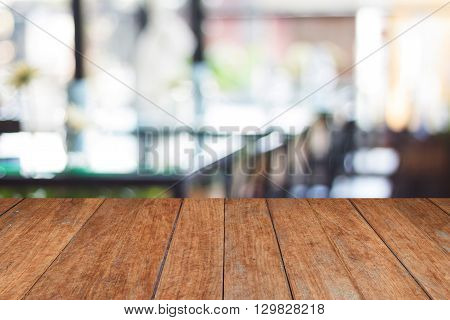 Empty wooden table and blurred cafe background, stock photo