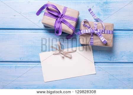 Empty tag and two festive gift boxes with presents on blue wooden background. Selective focus is on tag. Place for text.