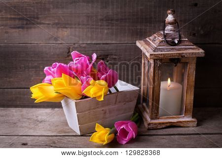 Pink and yellow spring tulips in box and candle in lantern on vintage wooden background. Selective focus.