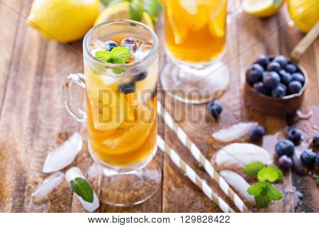 Iced tea with blueberries, lemon slices and mint on rustic background