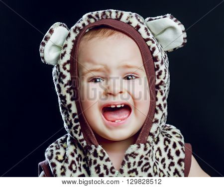 unhappy crying one year old baby, isolated against black background