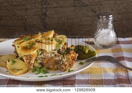 Homemade moussaka with herbs on a white plate close-up