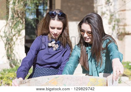 Smiling young women looking at travel map outdoor