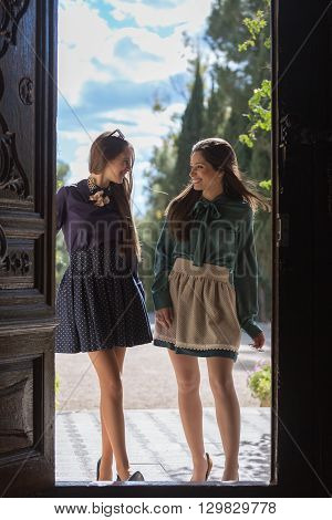 Two cheerful elegant women standing at door entrance and looking at each other