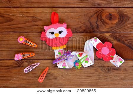 Organizer for hairpins, a felt owl, a set of barrettes. Kids crafts. Brown wooden background