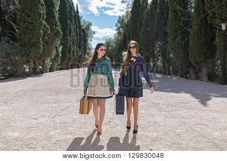 Elegant cheerful women with suitcases walking down the alley and smiling