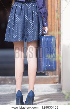 Back view of woman's legs in heels. Elegant woman holding blue suitcase