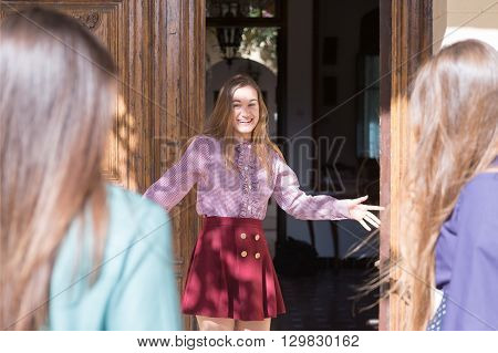 Young woman smiling while standing at door entrance guests are coming.