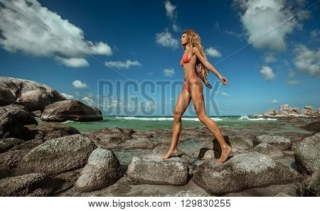 Young adult  girl on tropical beach. Flying Dreadlocks hair