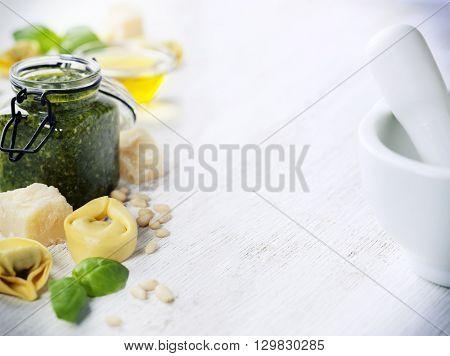 Homemade raw Italian tortellini with pesto on rustic wooden background