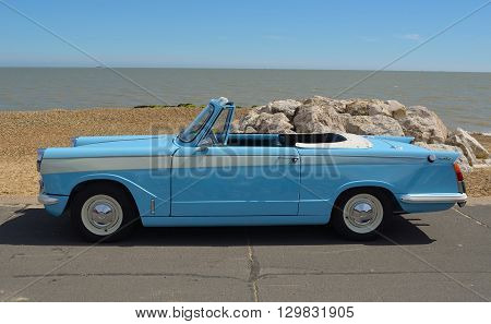 Felixstowe, Suffolk, England - May 01, 2016: Classic light Blue Triumph Herald open top motor car parked on seafront promenade.