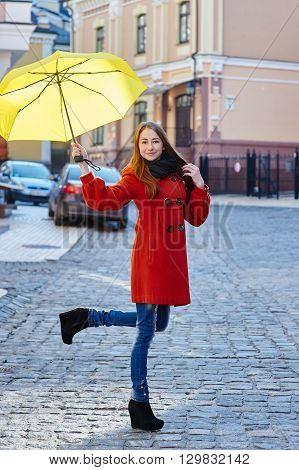 young woman in a red coat with yellow umbrella walks through the city.