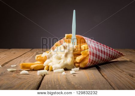 Tasty french fries whith mayonnaise on wooden table