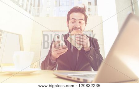 Toned picture of businessman eating hamburger and using mobile or smart phone while sitting in front of laptop computer.