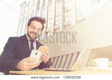 Toned picture of happy smiling businessman using mobile or smart phone. Happy freelance man in black business suit working in restaurant, eating hamburger.