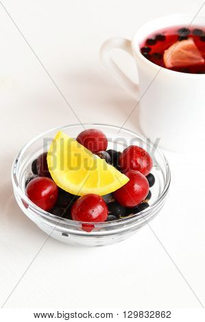 Frozen cherries and black currants, a slice of fresh lemon, Cup of fruit drink, dessert
