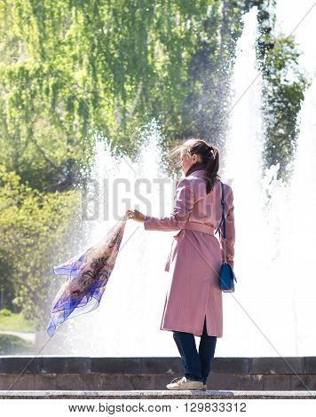 young girl in a coat with a handkerchief in the hand at the fountain