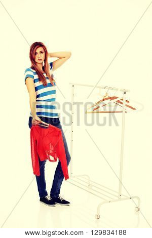 Confused teenage woman with nothing to dress