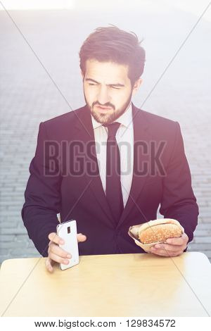 Toned portrait of handsome businessman eating junk food and holding mobile or smart phone while having break in cafe during his work.