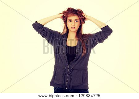 Young surprised woman holding hands inside hair