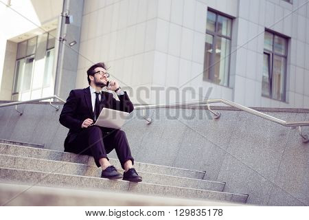 Toned picture of confident businessman speaking over mobile or smart phone and working on his laptop computer while sitting on stairs in city centre.