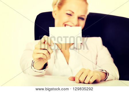Smile business woman sitting behind the desk and holding empty buisiness card