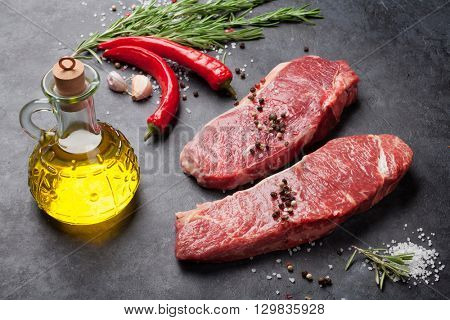 Raw striploin steak with salt and pepper cooking over stone table