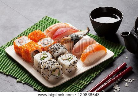 Set of sushi, maki and green tea on stone table