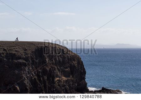 Scenic large rock overlooking the sea. Bicyclist on a background of sky and stone, Papagayo beach Lanzarote