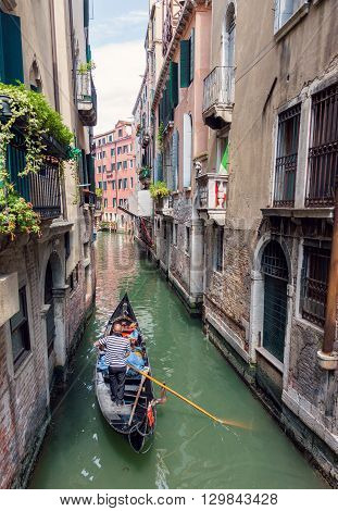 VENICE ITALY - MAY 27 2015: Traditional venetian gondola sailing tourists in remote canal in Venice Italy