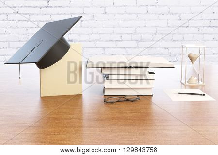 Graduation concept with book graduation cap hourglass and spectacles on wooden desktop with brick wall in the background. 3D Rendering