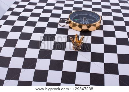 Retro Compass with a crown on a checked background