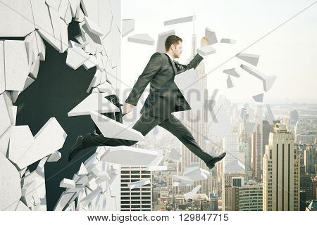 Business breakthrough success concept with man jumping through wall on city background