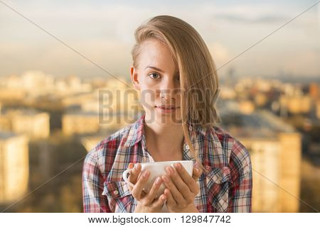 Gorgeous european girl with side swept hair drinking coffee on blurry city background