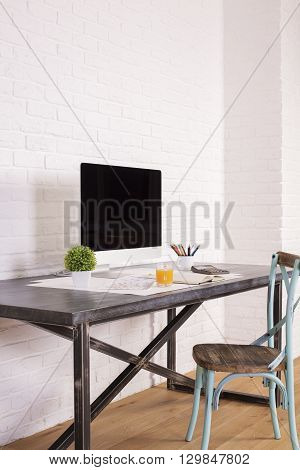 Sideview of antique chair at designer desk with computer screen and other items on white brick background