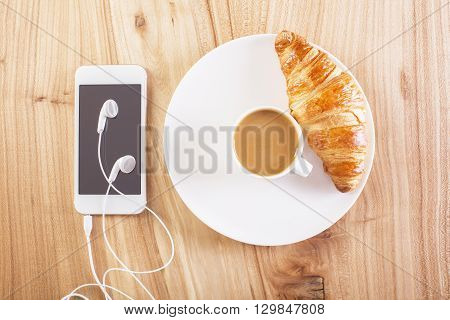 Topview of wooden desktop with phone headphones plate with coffee and croissant