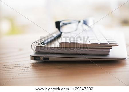 Side view of spectacles keyboard pen notepads and laptop