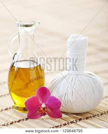 Orchid, jar with oil and massaging ball on woven bamboo mat over isolated background.