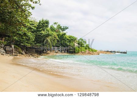 Scene of idyllic beach and forest with an old bridge.