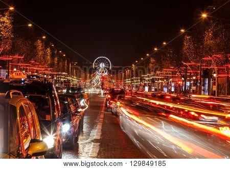 December illumination and traffic lights on the Avenue des Champs-Élysées in ParisEurope. In the distance you can see the Ferry wheel located in Place de la Concorde.