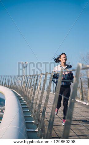 Beautiful Hispanic Woman Running On A Bridge